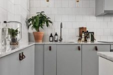 14 an inviting Scandinavian space with light grey cabinets with leather pulls and white tile walls