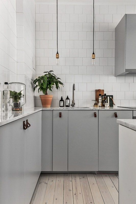 an inviting Scandinavian space with light grey cabinets with leather pulls and white tile walls