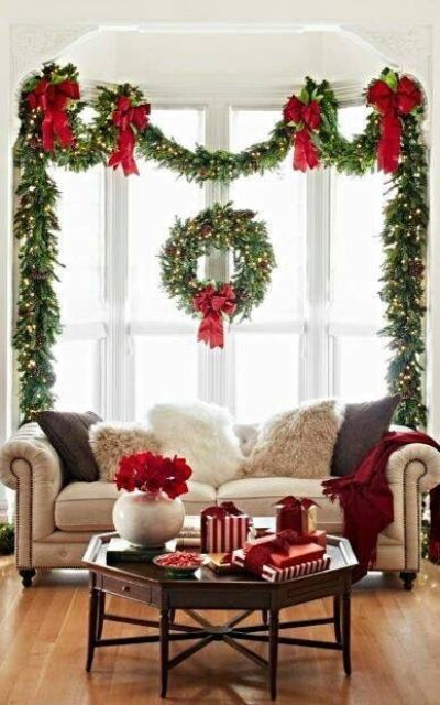 style your window with a lush evergreen garland with red bows, pinecones and lights to make the living room inviting