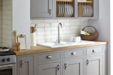15 a traditional light grey kitchen with white tiles and light-colored natural wood looks very cozy and inviting