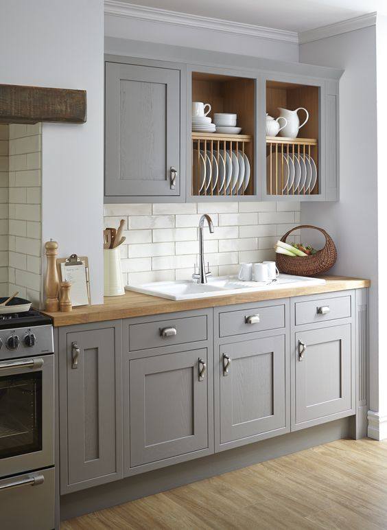 a traditional light grey kitchen with white tiles and light-colored natural wood looks very cozy and inviting