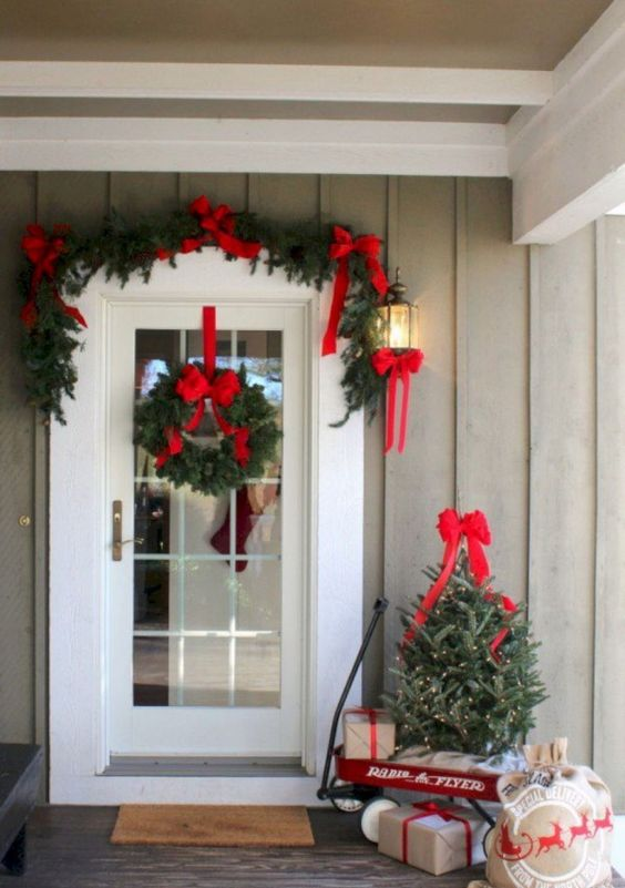an evergreen garlnd with red bows, a matching wreath and a little Christmas tree for a bright and welcoming porch