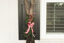 15 vintage skis decorated with evergreens, fake berries nd a plaid bow for a winter porch