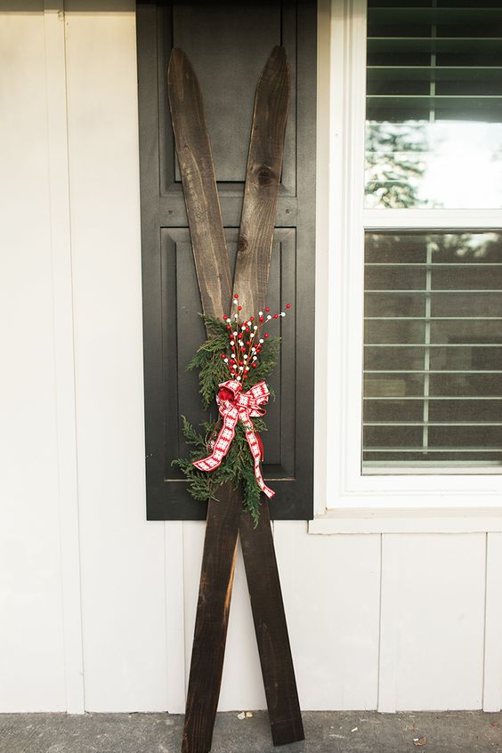 vintage skis decorated with evergreens, fake berries nd a plaid bow for a winter porch