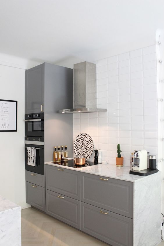 a stylish contemporary space with grey cabinets, a white tile backsplash and a stainless steel hood looks airy