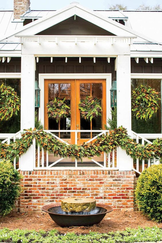 evergreen garlands with pinecones and foliage can be used for styling railing and matching wreaths on the windows