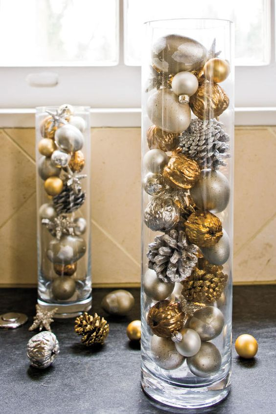 tall glass vases filled with snowy pinecones and metallic ornaments and nuts for festive decor