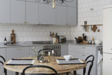 17 a simple modern light grey kitchen is psruced up with a gorgeous chandelier and a stylish dining set with black touches