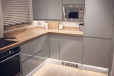 18 a small minimalist light grey kitchen with wooden countertops, sleek shiny cabinets and additional lights under that make it look bigger