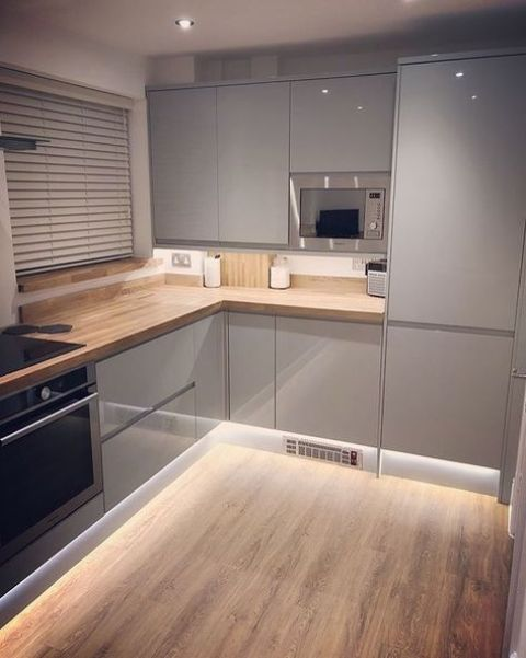 a small minimalist light grey kitchen with wooden countertops, sleek shiny cabinets and additional lights under that make it look bigger