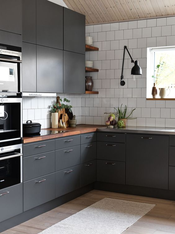 a contemporary graphite grey kitchen with white tiles and rich-colored wooden countertops to refresh