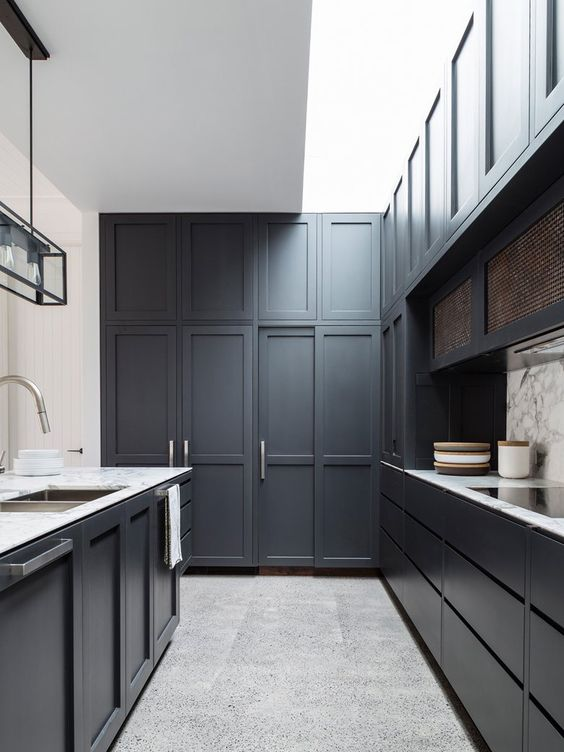 a graphite grey kitchen with sculptural panelling and a marble backsplash and countertops