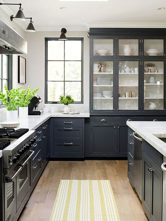 a graphite grey traditional kitchen with stainless teel accents and appliances and vintage lamps
