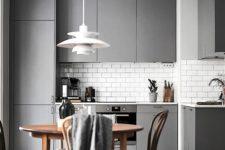 22 a Scandinavian sleek grey kitchen with elegant tall cabinets, a white tile backsplash and a statement pendant lamp