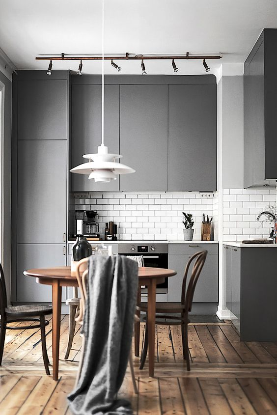 a Scandinavian sleek grey kitchen with elegant tall cabinets, a white tile backsplash and a statement pendant lamp
