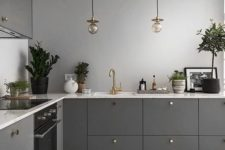 25 a stylish contemporary kitchen in graphite grey cabinets, grey walls and stainless steel appliances