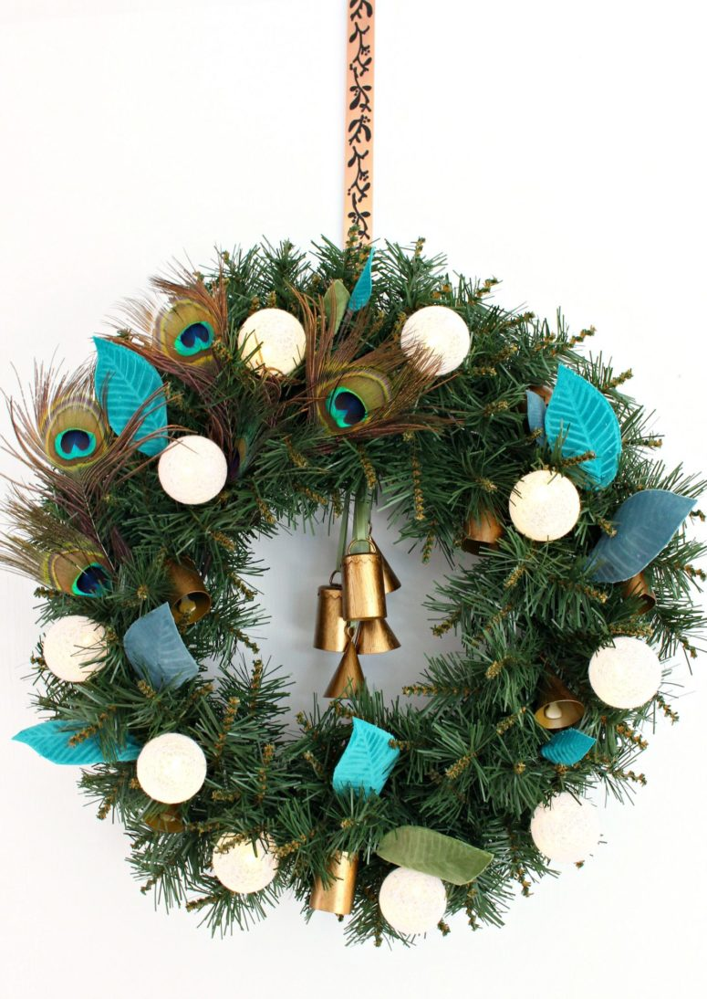 DIY boho lux Christmas wreath with peacock feathers and bells (via www.danslelakehouse.com)
