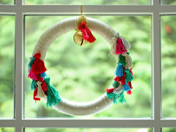 DIY colorful Christmas boho wreath with tassels and jingle bells (via www.diynetwork.com)