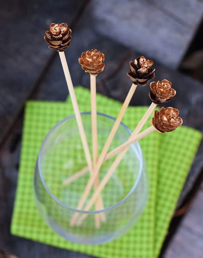 DIY gilded pinecone drink stirrers for holidays (via helloglow.co)
