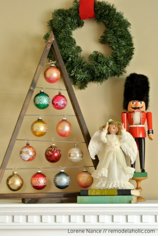 DIY A-framed Christmas tree ornament display with colorful ornaments (via www.remodelaholic.com)