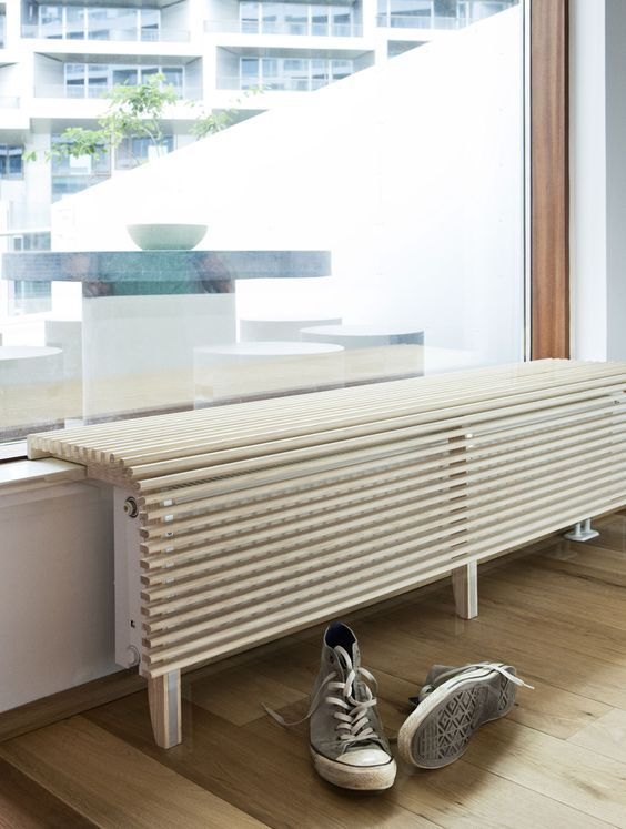 a super cool curved wooden plank screen creates an additional seat and covers the radiator too