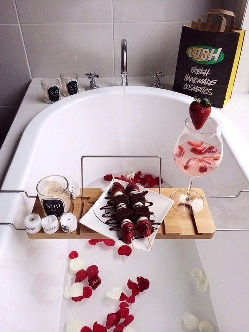 rose petals in the bathtub, a caddy with candles, strawberries and chocolate plus a strawberry cocktail