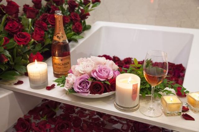 a caddy with pink wine, candles and fresh roses in a plate and red rose petals in the bathtub