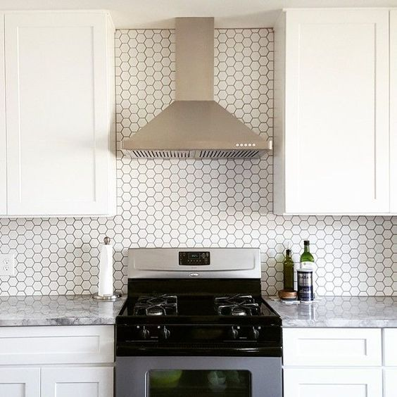 small scale white hexagon tiles with black grout stand out and make the backsplash eye-catchy