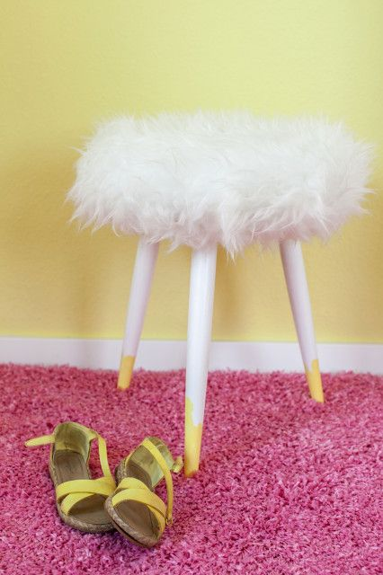 a simple three-legged stool renovated using bright yellow paint and Tejn fur from IKEA