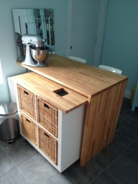 IKEA Kallax kitchen island with a countertop and a mobile part with wicker baskets as drawers