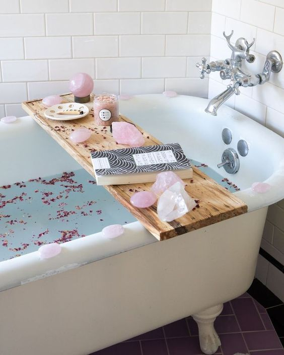 some pink petals in the bathtub, pikn geodes on the caddy and pink candles for a cute Valentine's Day look