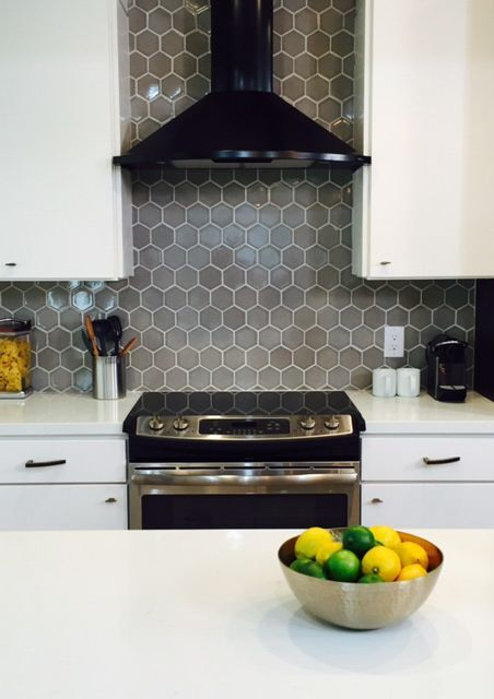 a grey hex tile kitchen backsplash with white grout adds color to the space and make it catchier
