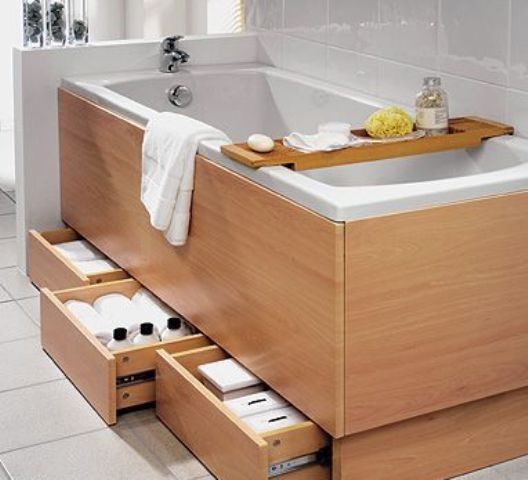 a bathtub clad with wood with several drawers under the bathtub for smart and comfy storage