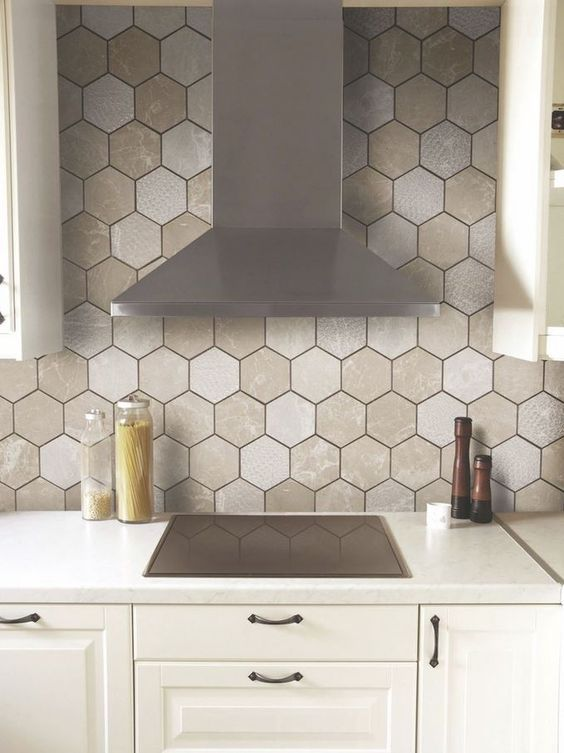 a hex tile backsplash in various neutral shades and with black grout makes a neutral space interesting