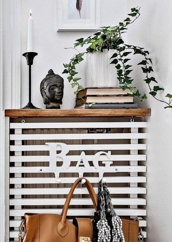 a simple and stylish plank screen with bag hooks and a wooden top for storage is ideal for entryways