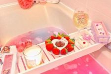 11 a lush pink bubble bath with pink accessories, sweets, a candle, a magazine and some fresh strawberries