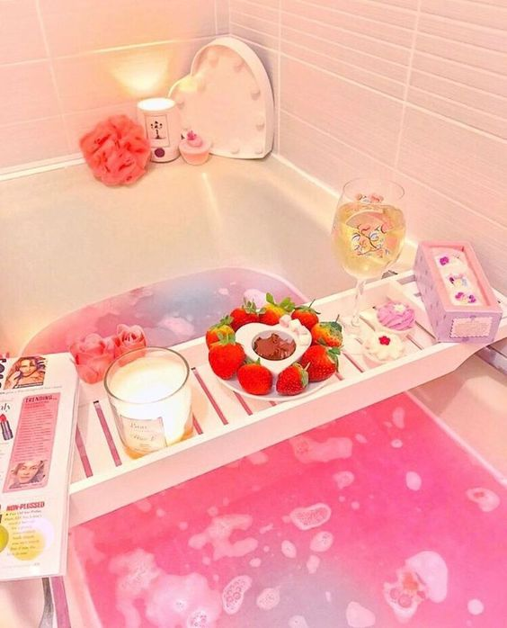 a lush pink bubble bath with pink accessories, sweets, a candle, a magazine and some fresh strawberries