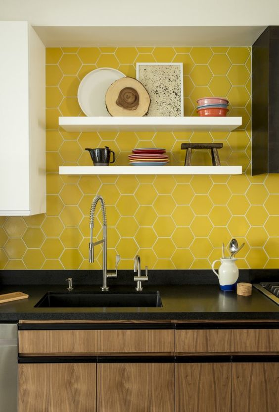 bold yellow hex tiles with white grout accent the black cabinets and add color to the space