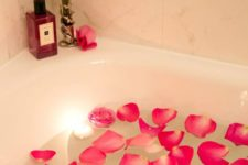 12 pink petals and peonies in the bath, floating candles, a bloom arrangement on the corner of the bathtub