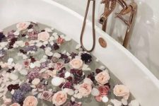 13 various blooms in dark and light pink tones and floating candles will immediately turn your bathtub into a sanctuary