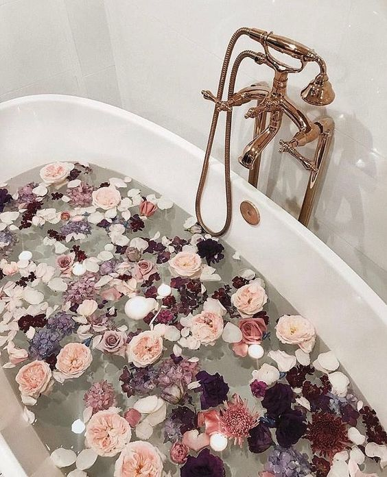 various blooms in dark and light pink tones and floating candles will immediately turn your bathtub into a sanctuary