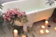 14 a bathtub decorated with pink blooms and ferns, candles on the floor and some wine