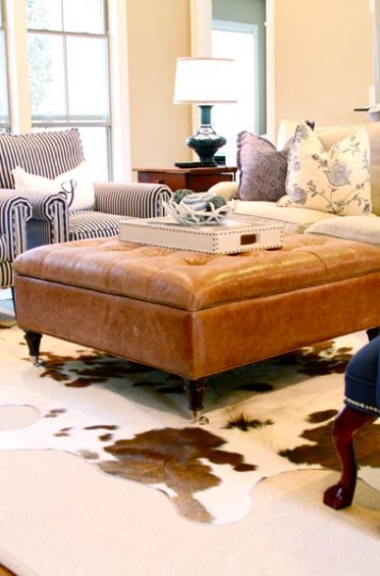 an amber tufted ottoman with storage on wooden legs is a great way to add a refined touch