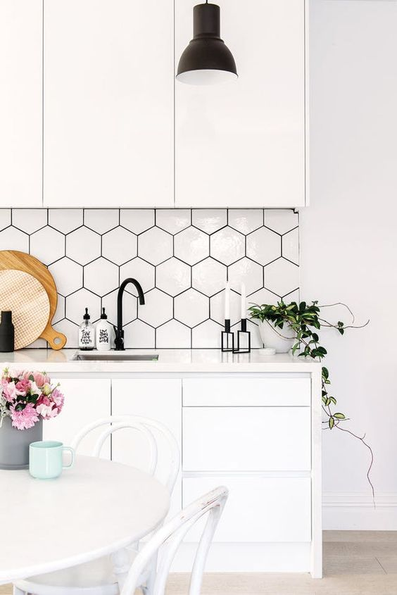 large scale white hexagon tiles with black grout make a perfect match for a minimalist or Scandinavian kitchen