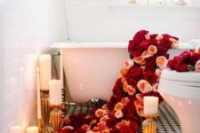 15 lush red and peachy blooms going down to the floor and petals on the floor, candles all around