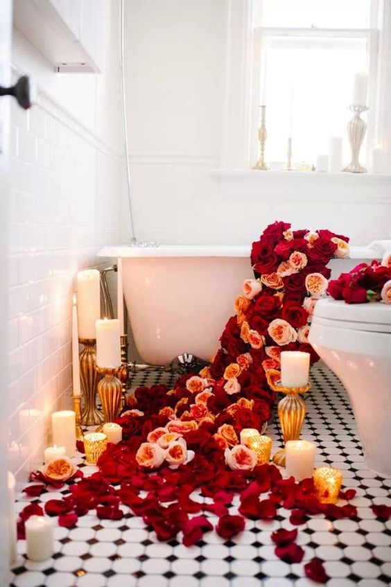 lush red and peachy blooms going down to the floor and petals on the floor, candles all around