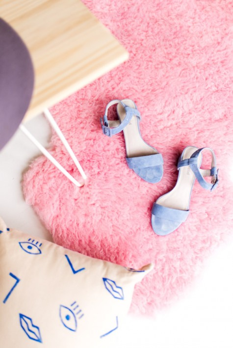 DIY pink faux fur sheepskin rug from IKEA painted pink adds a girlish fele to the space