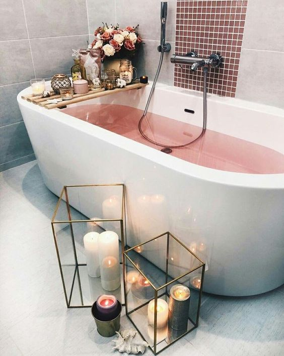 pink water in the bathtub, candles including aromatic ones, white and pink blooms and large lanterns with candles