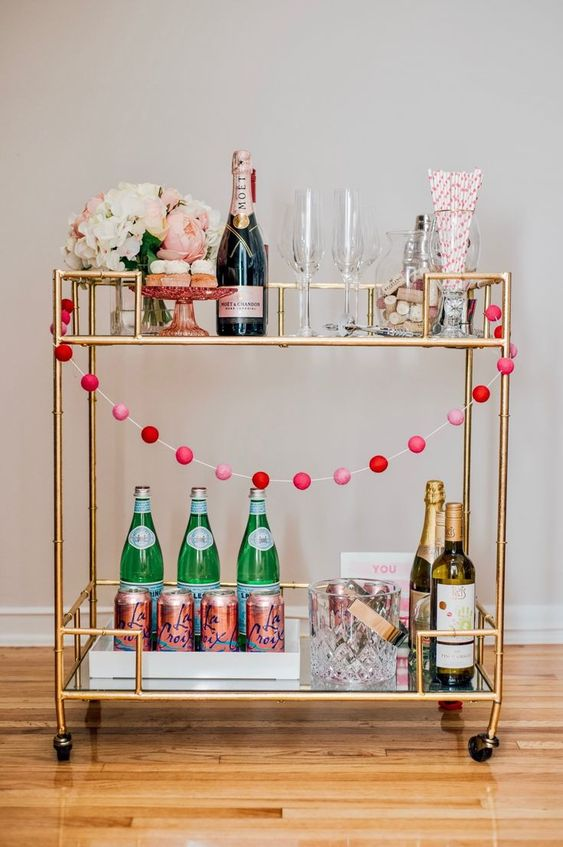a Valentine bar cart styled with a pink pompom garland and a centerpiece of candy-colored blooms