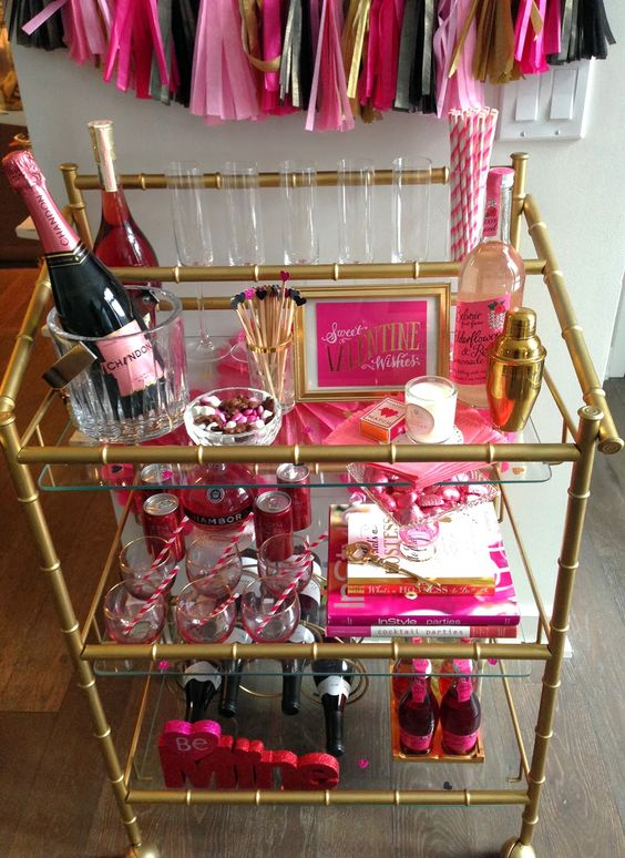 a bar cart styled in hot pink - with hearts, bottles, drink stirrers and fun candies for Valentine's Day